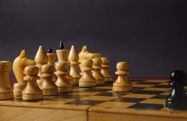 Играет в деревянные шахматы. белая пешка против остальных фигур на доске