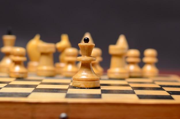 Играет в деревянные шахматы. белая королева на фоне остальных фигур на доске