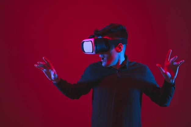 Играли в vr-гарнитуре. портрет кавказского молодого человека, изолированные на красной стене в неоновом свете. красивая модель. понятие человеческих эмоций, мимики, молодости, устройств.