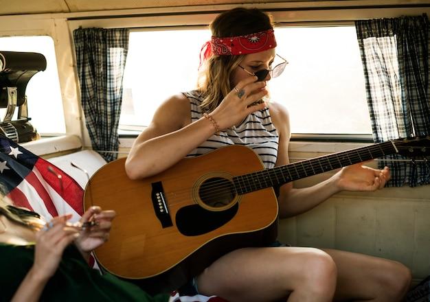 女性一緒に友達と一緒にロードトリップにplayinhギター