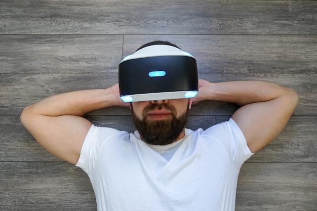 ソニーplaystation vrヘッドセットによって仮想眼鏡で彼の背中に横になっている成人男性