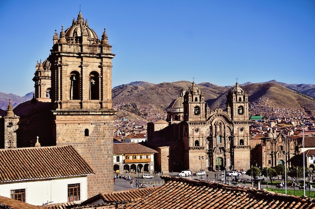 Plaza de armas, cathedral and church of the society of jesus or iglesia de la compania de jesus. cusco, peru. blue sky in a beautiful summer day.