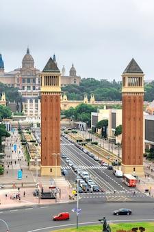 Площадь испании, венецианские башни и национальный дворец в барселоне, испания. облачное небо, движение