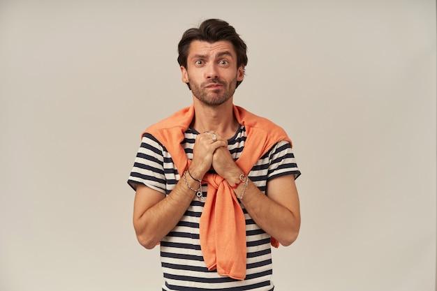 ブルネットの髪と剛毛で懇願する男。ストライプのtシャツを着て、オレンジ色のセーターを肩に結んでいます。ブレスレット、リングがあります。手のひらを一緒に保持します