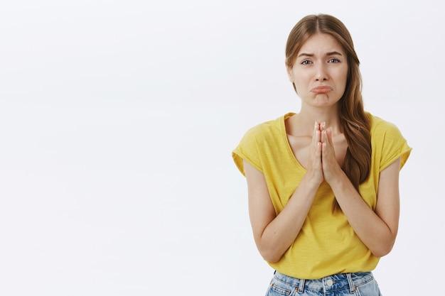 Умоляющая надутая девушка умоляет о помощи, просит извинений и грустно гримасничать