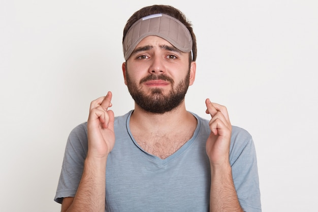 Pleading upset annoyed man looking directly  crossing his fingers, wearing sleeping mask, having problems with sleeping