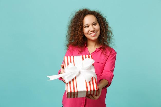 ピンクの服を着た楽しいアフリカの女の子は、青いターコイズブルーの壁の背景に分離されたギフトリボンと赤い縞模様のプレゼントボックスを保持します。国際女性の日の誕生日の休日の概念。コピースペースをモックアップします。