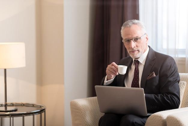 노트북 앞에 호텔에 앉아있는 동안 컵을 들고 커피를 마시는 즐거운 세 수염 사업가