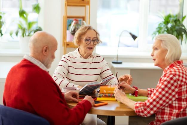 Приятные пожилые люди обсуждают свои любимые книги, давая друг другу рекомендации