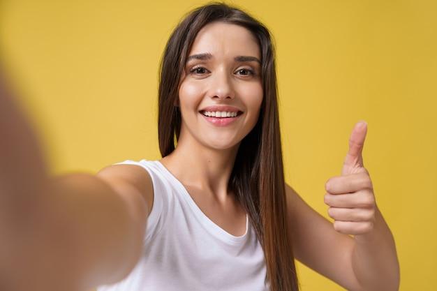 スタジオで自分撮りをして笑っている楽しい魅力的な女の子。明るい黄色の背景に自分の写真を撮る茶色の髪の格好良い若い女性。