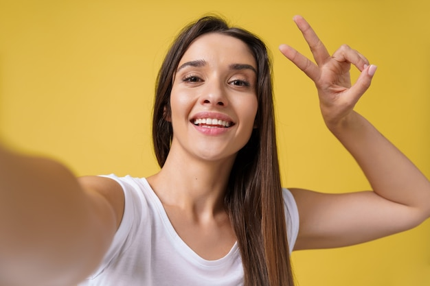 Pleasant attractive girl making selfie in studio and laughing. good-looking young woman with brown hair taking picture of herself on bright yellow background.
