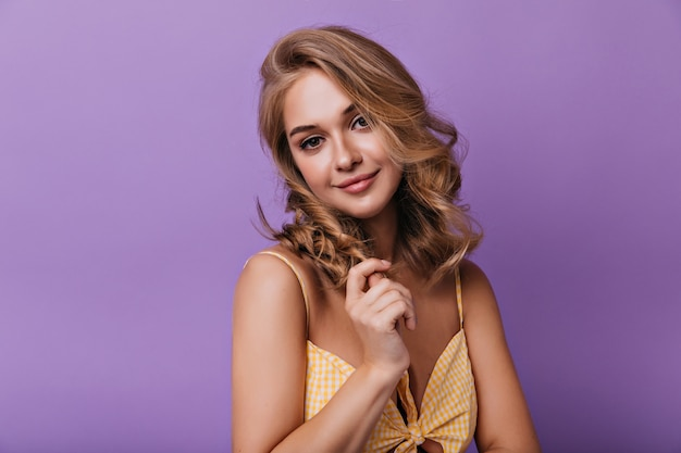 Pleasant blonde woman posing on bright with gently smile. portrait of debonair lady standing in front of purple wall.