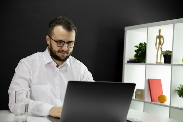 Pleasant businessman surfing the net in cozy office workplace. working at home