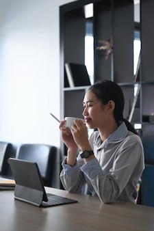 Pleasant businesswoman holding cup of hot coffee during coffee breaking in office.