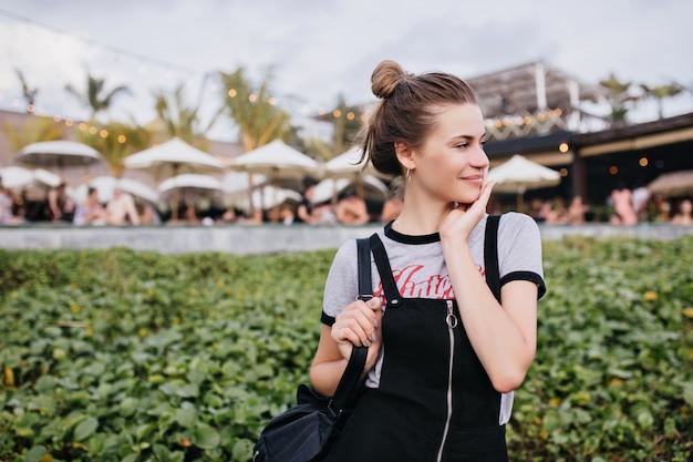 Piacevole ragazza caucasica in posa con un timido sorriso sulla natura. foto di adorabile modello femminile con acconciatura carina che riposa nella città di villeggiatura.