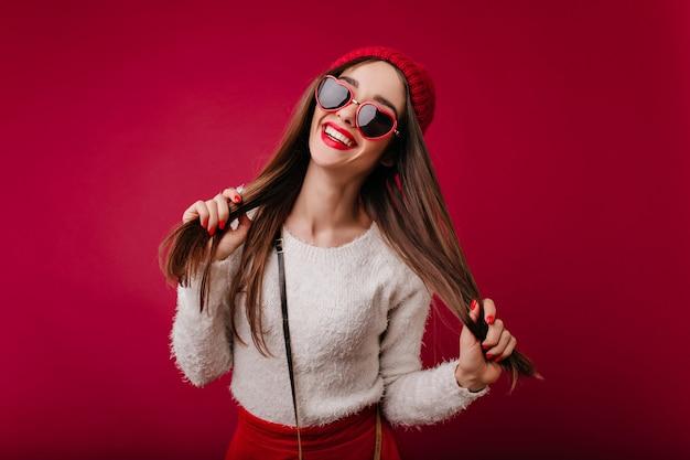 Piacevole ragazza caucasica in cappello rosso isolato su spazio bordeaux
