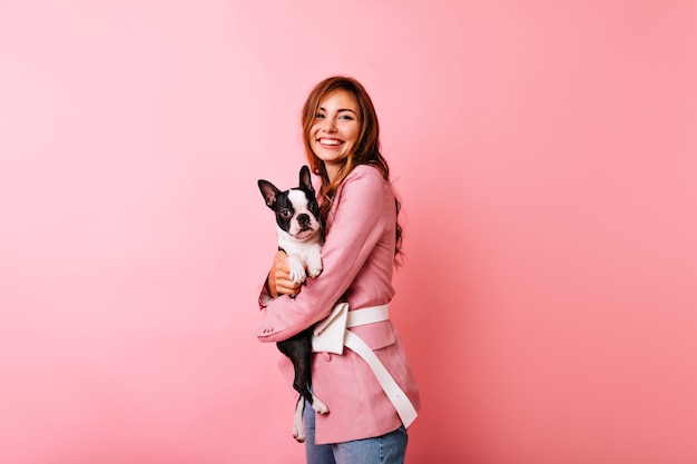 Pleasant caucasian woman in pink attire embracing puppy. glamorous white girl holding french bulldog with smile.