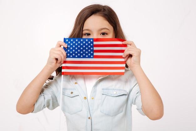 Приятный очаровательный ребенок демонстрирует американский флаг, выражая положительные эмоции и стоя у белой стены