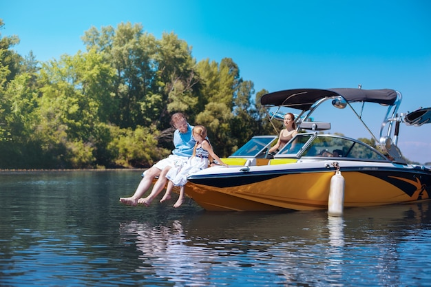 Pleasant chat. loving young father and his beloved little daughter sitting on the bow of the boat and chatting together