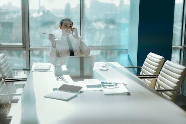 楽しいチャット。会議室の空のテーブルに座って、仕事の休憩中に電話で誰かと楽しくおしゃべりしている明るい若い労働者