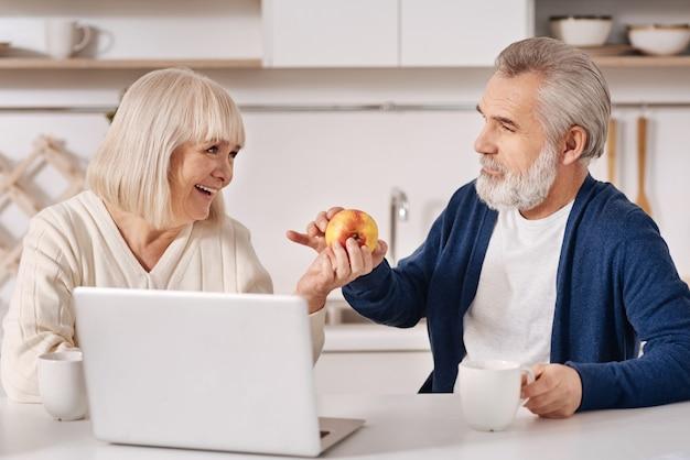 ノートパソコンの前に家で座って、愛を表現し、お互いを見ながらリンゴを持って、楽しく陽気な魅力的な老夫婦