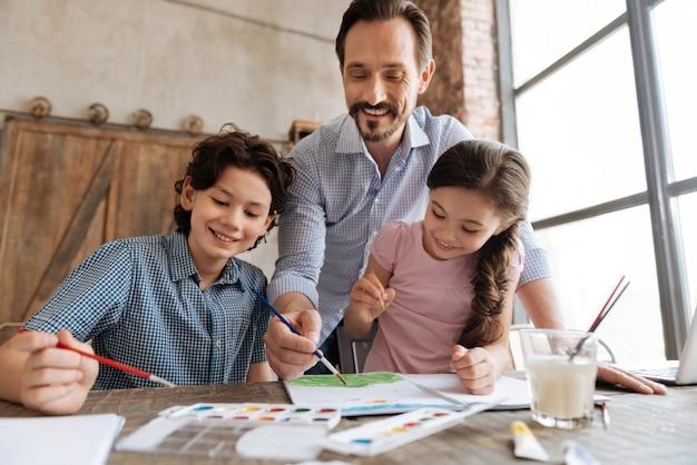 お互いに絆を深め、美しい水彩画を一緒に作りながら、幸せそうに見える楽しい陽気な家族。