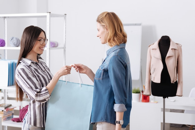 아틀리에 방에 서서 큰 파란색 가방을 들고 배경에 분홍색 재킷이 달린 마네킹을 들고 즐거운 쾌활한 여성