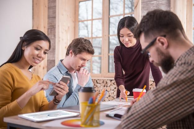Приятное сотрудничество. позитивно довольные молодые люди сидят вместе и сосредотачиваются на своем проекте, работая в команде