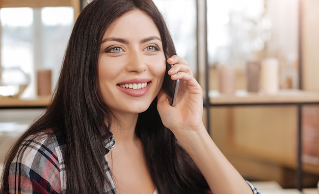 Pleasant communication. joyful attractive young woman speaking on the phone and smiling while being in a wonderful mood