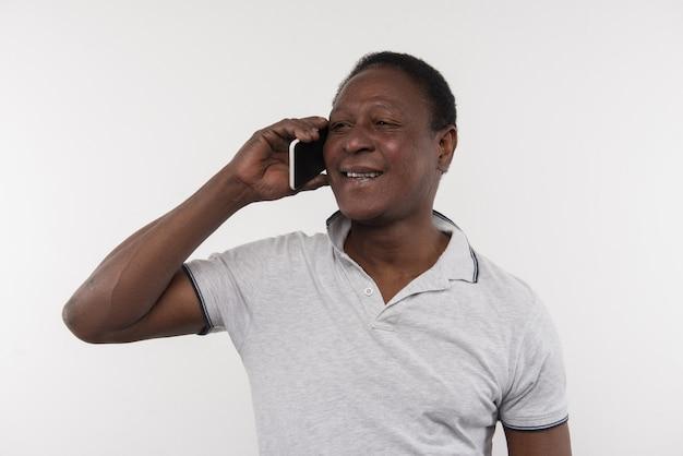 즐거운 의사 소통. 전화 통화하는 동안 귀에 전화를 씌우고 즐거운 멋진 남자
