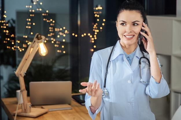 楽しいコミュニケーション。彼女のオフィスに立って、彼女の仕事の日を終えている間電話で話している素敵な陽気な女性医師