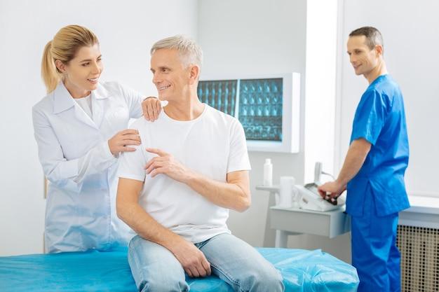 Приятное общение. хороший веселый позитивный мужчина сидит в кабинете врача и разговаривает со своим терапевтом в позитивном настроении