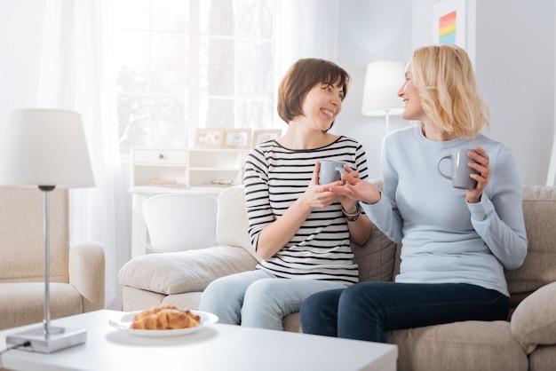 즐거운 의사 소통. 즐거운 대화를 나누면서 함께 앉아 차 한잔 들고 좋은 행복 기뻐 여성