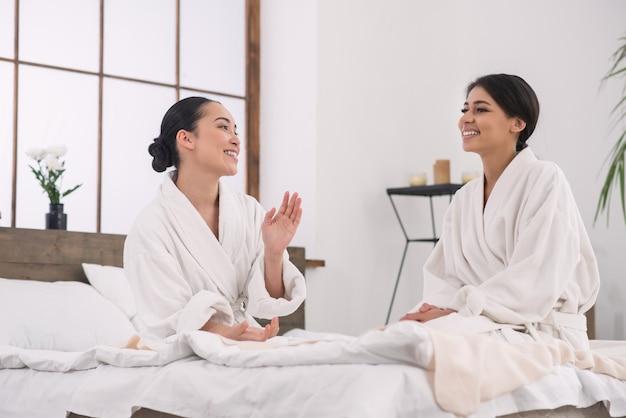Приятное общение. позитивно довольные друзья разговаривают друг с другом, находясь в спа-салоне