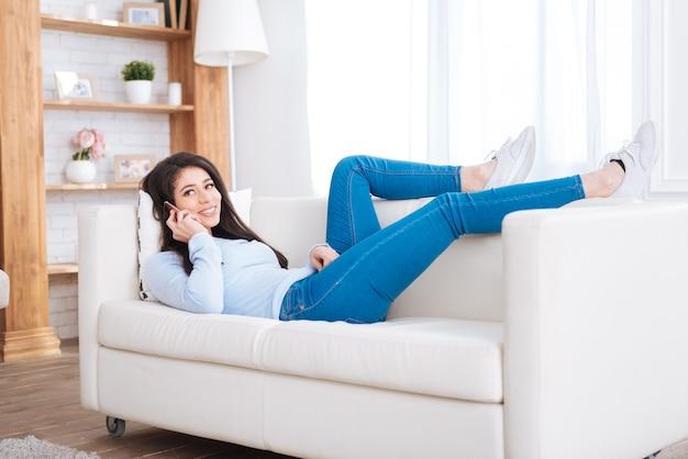 즐거운 대화. 소파에 누워있는 동안 전화로 이야기하는 행복 한 활기찬 여자