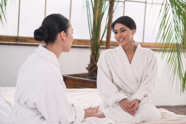 Приятный разговор. позитивные счастливые друзья разговаривают друг с другом, проводя время в спа-салоне