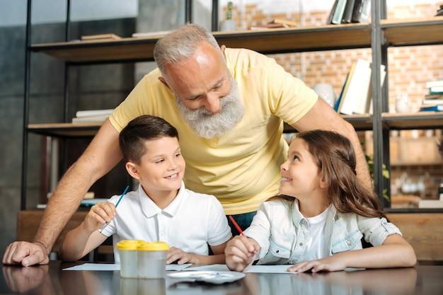 楽しい会話。甘いプレティーンの男の子と女の子がテーブルに座って、絵を描いたり、思いやりのある祖父と話したりするためのブラシを持っています