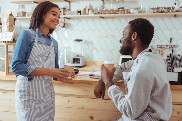 楽しい会話。紙コップからコーヒーを飲み、仕事を休んでいる間、お互いに話している明るい楽しい若いバリスタ