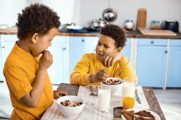 즐거운 대화. 아침 식사로 시리얼을 먹으면서 테이블에 앉아 서로 대화를 나누는 경쾌한 10 대 초반 소년