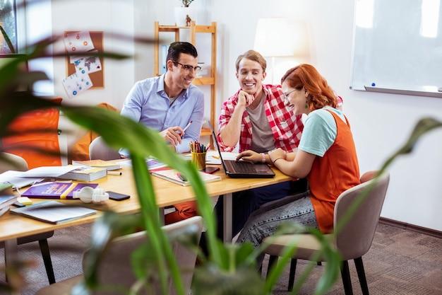 즐거운 협력. 팀에서 함께 작업하는 동안 웃 고 즐거운 젊은 사람들