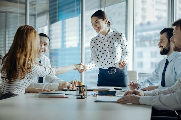 楽しい協力。明るい若い女性の上司が同僚と握手し、昇進を祝い、会議を行っている