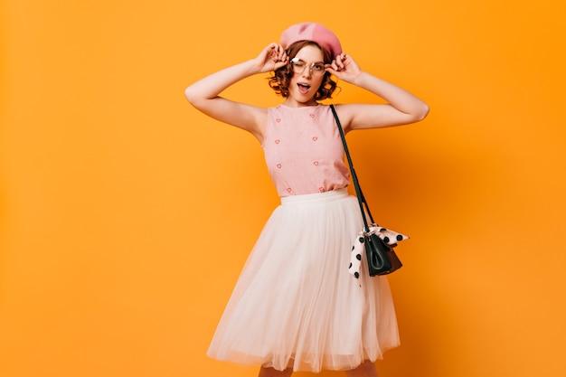 Приятная кудрявая женщина в очках, глядя на камеру. студия сняла французскую женскую модель, позирующую на желтом фоне.