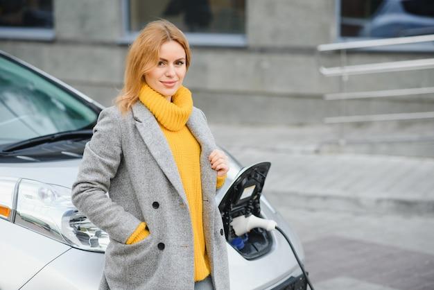 그것을 충전 하 고 옆으로 찾고 그녀의 차에 기대어 즐거운 귀여운 금발 여자.