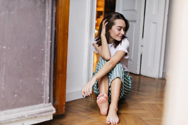 Piacevole ragazza dai capelli scuri che trascorre la mattinata a casa. foto dell'interno della signora bruna allegra in pigiama seduto sul pavimento.
