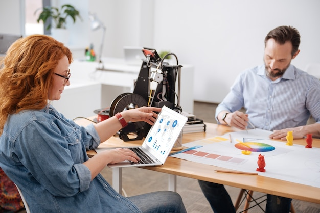 ノートパソコンの画面を見て、オフィスで働いている間統計を勉強して楽しい喜んで魅力的な女性