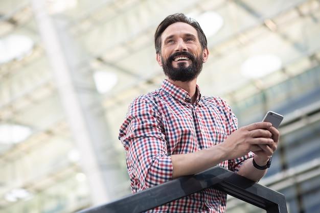 Приятный довольный улыбающийся мужчина смотрит в сторону, держа в руке телефон