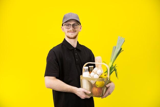 Приятный курьер держит корзину с фермерскими эко продуктами, службой доставки еды