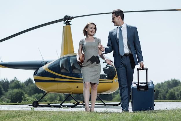楽しい議論。ヘリポートを離れ、ヘリコプターから離れながらおしゃべりする陽気なビジネスパートナー