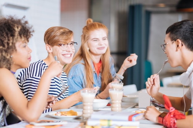 Pleasant discussion. positive delighted boy keeping smile on his face while eating dessert