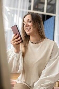 スマートフォンの白い料理のインテリアを使用して、モダンなキッチンでリラックスできる快適な国内女性
